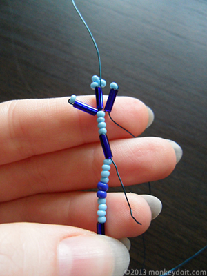 Slide the wire down through the small seed beads and the next bugle bead
