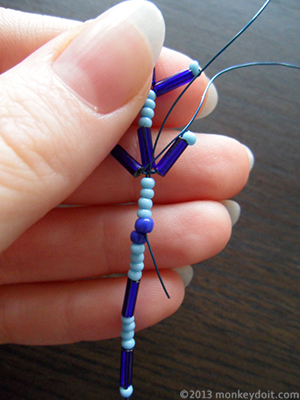 Push the wire towards the centre so that you come out in between the large seed beads