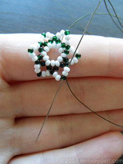 Go through the beads in front of the needle so that you come out through the uppermost bead