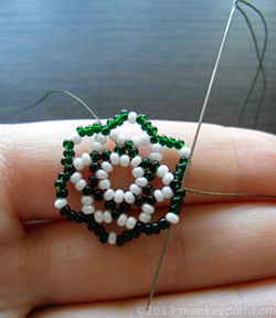 Push the needle up again so that it comes out through the bead in the middle