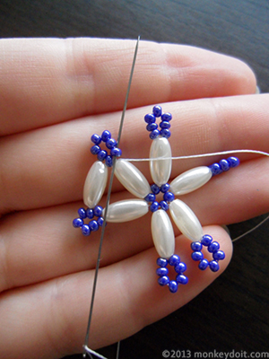 Push the needle up through the seed bead on the other side