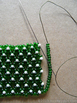 String as many beads as you need to reach the opposite end of the row and push the needle through bead A