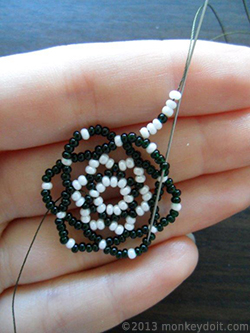 Skip five beads underneath and push the needle through the sixth one