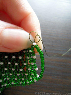 Tie a knot at the base of the bead