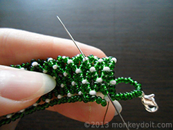 Weave the thread through a couple of beads in any direction to bury the knot and cut the remaining thread as close to the beads as possible