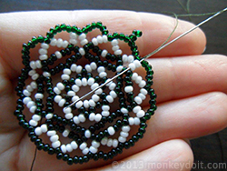 Weave the thread through a couple of beads in any direction to bury the knot