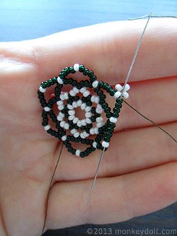 Bring the needle through the side of the earring to reach the next bead A