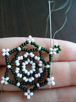 Weave the thread through several beads to bury the knot and cut the thread end as close to the beads as possible