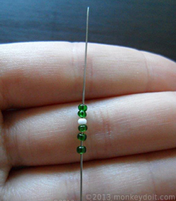 three green beads followed by one white bead, then two green beads