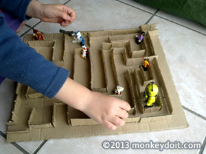 Child playing with cardboard maze with figurines