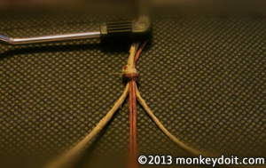 Clip looped hemp cords under the paper holder of a clip board