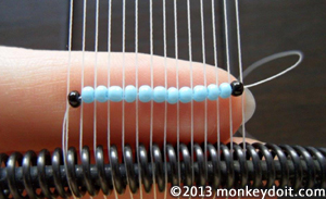 Fit the beads into the spaces between the warp threads