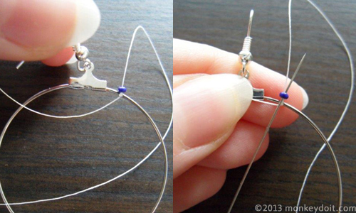 Thread wrapped around the hooped earring and needle through the bead